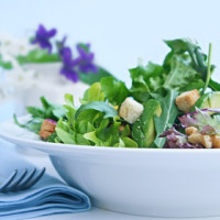 Green salad in a white bowl, with flowers behind.