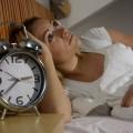 Junge Frau liegt nachdenklich im Bett