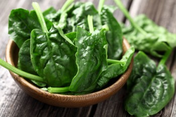 Spinach leaves in a wooden plate